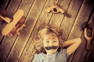 32499375 - hipster kid with vintage wooden toys at home. girl power and feminism concept