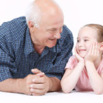 41041584 - portrait of a grandfather wearing blue checkered shirt and his small pretty granddaughter lying near looking at each other and smiling, isolated on a white background