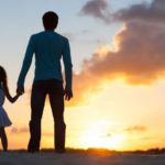 19294655 - father and little daughter silhouettes on beach at sunset